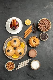 Draufsicht leckere kekse mit tasse tee auf der dunklen oberfläche kuchen kuchen zucker dessert keks tee