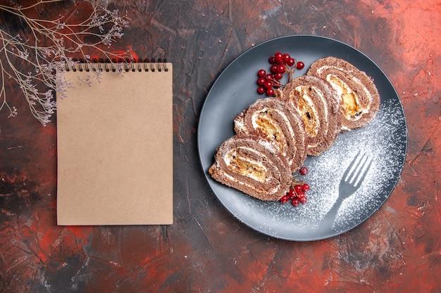 Draufsicht leckere keksrollen mit früchten auf dunklem hintergrund
