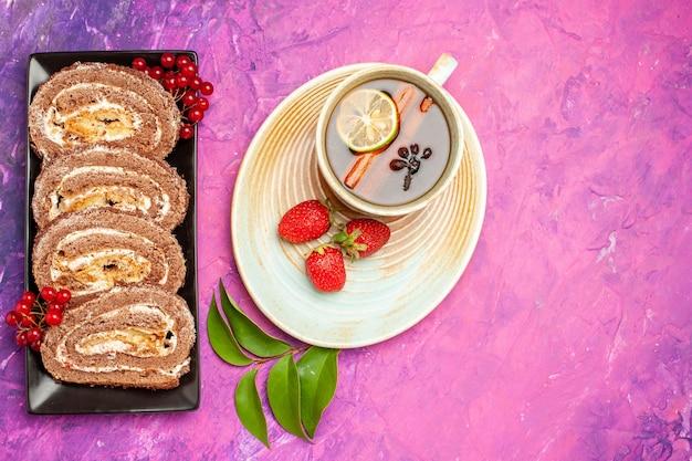Draufsicht leckere keksrollen mit tasse tee auf rosa hintergrund