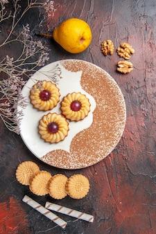 Draufsicht leckere kleine kekse innerhalb platte auf dem dunklen tischkuchen süßen kekse zucker