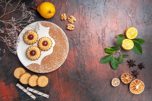Draufsicht leckere kleine kekse mit früchten auf dunklem tischkuchen süßer kekszucker