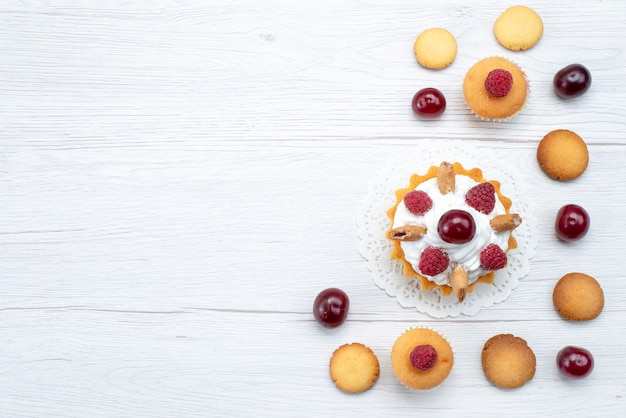Draufsicht leckere kleine kuchen mit himbeeren zusammen mit keksen und kuchen auf dem hellen hintergrundkuchenkeks süße beere backen frucht