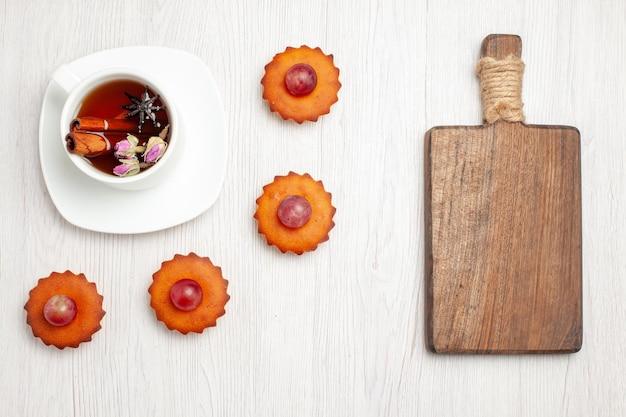 Draufsicht leckere kleine kuchen mit tasse tee auf weißer oberfläche dessertplätzchen keks teekuchen kuchen