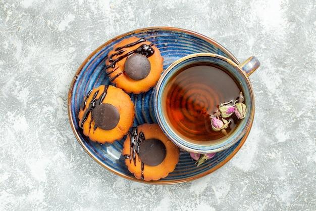 Draufsicht leckere kleine kuchen mit tasse tee auf weißer oberfläche kuchen keks keks dessert tee süß