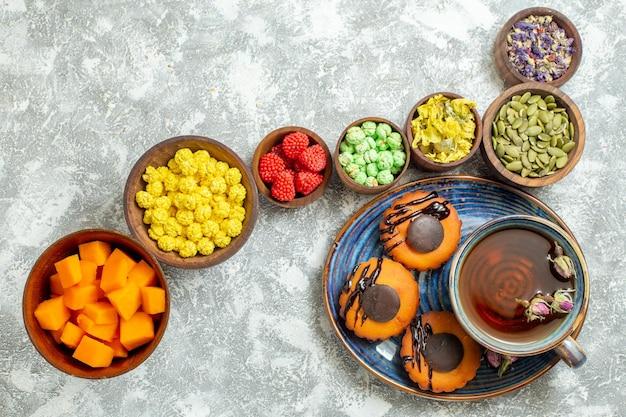 Draufsicht leckere kleine kuchen mit tasse tee und bonbons auf weißer oberfläche kuchen keks keks dessert süßer tee