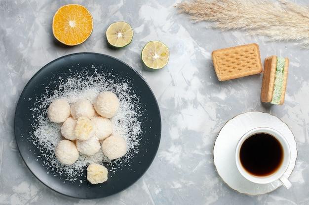 Draufsicht leckere kokosnussbonbons mit tasse tee auf weiß