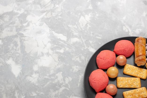 Draufsicht leckere kuchen mit bagels und bonbons auf grauweißem schreibtisch