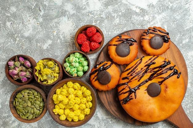 Draufsicht leckere kuchen mit schokoladenglasur und bonbons auf weißer oberfläche kuchen keks dessert süßer kekskuchen