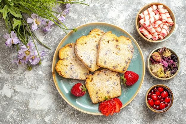 Draufsicht leckere kuchenscheiben mit erdbeeren auf licht