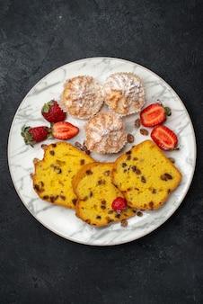 Draufsicht leckere kuchenscheiben mit frischen roten erdbeeren auf dunkelgrauer oberfläche