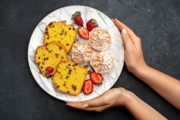 Draufsicht leckere kuchenscheiben mit frischen roten erdbeeren und keksen auf der grauen oberfläche