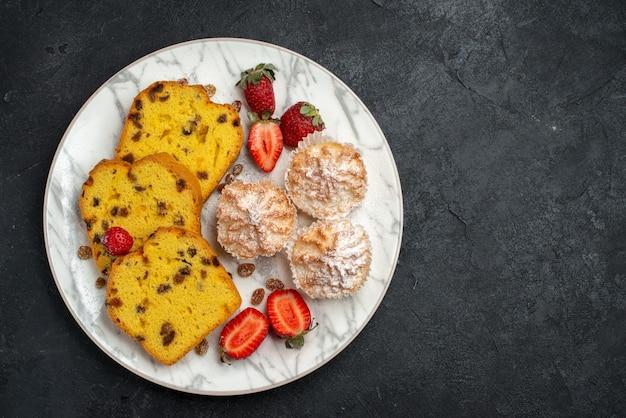 Draufsicht leckere kuchenscheiben mit frischen roten erdbeeren und keksen auf dunkelgrauer oberfläche