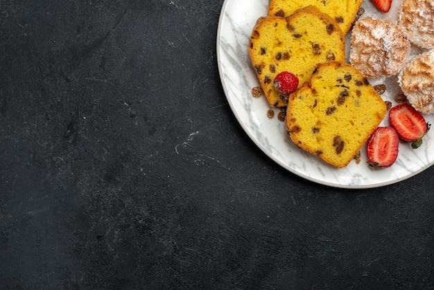 Draufsicht leckere kuchenscheiben mit frischen roten erdbeeren und keksen auf grauem schreibtisch