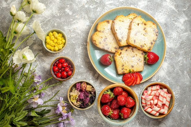 Draufsicht leckere kuchenscheiben mit früchten und bonbons auf licht