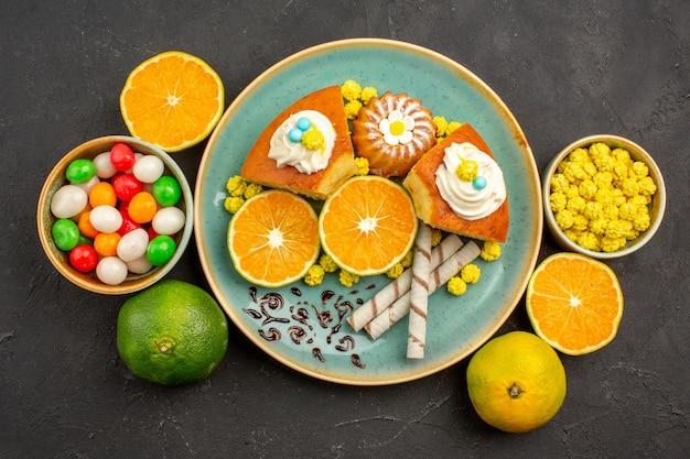Draufsicht leckere kuchenstücke mit frisch geschnittenen mandarinen und süßigkeiten auf dunkelheit