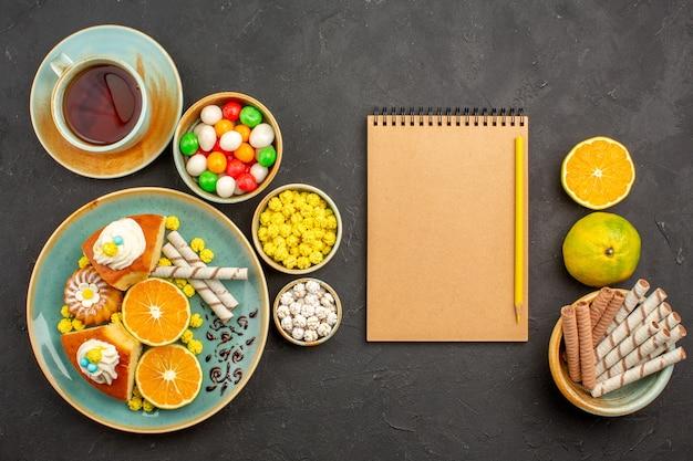 Draufsicht leckere kuchenstücke mit frischen mandarinen und einer tasse tee im dunkeln