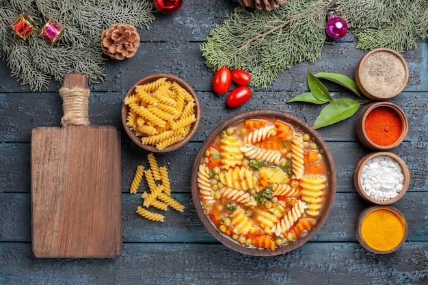 Draufsicht leckere nudelsuppe aus spiralförmiger italienischer pasta mit gewürzen auf einer dunkelblauen rustikalen schreibtischsuppe mit farbe gericht pasta