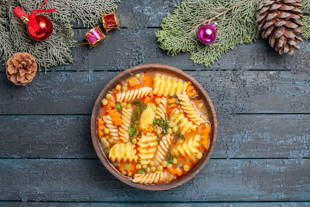 Draufsicht leckere nudelsuppe aus spiralförmiger italienischer pasta mit grüns auf dem dunkelblauen schreibtisch küche nudelsuppe farbgericht abendessen