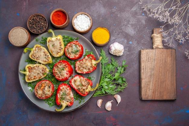 Draufsicht leckere paprika köstliche gekochte mahlzeit mit fleischgemüse und gewürzen auf dem dunklen oberflächengericht abendessen essen