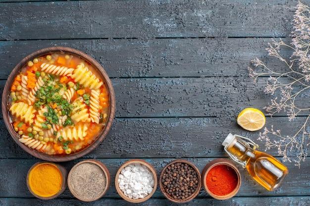 Draufsicht leckere pastasuppe aus spiralförmiger italienischer pasta mit gewürzen auf dem dunkelblauen schreibtischsaucengericht italienische pastasuppe