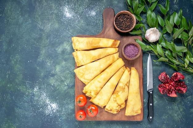 Draufsicht leckere pfannkuchen auf dunkelblauem hintergrund gerollt fleischgebäck hotcake teig kuchenfarbe süße kuchenmahlzeit