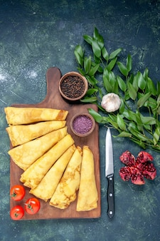 Draufsicht leckere pfannkuchen auf dunklem hintergrund gerollt kuchen fleisch gebäck hotcake teig farbe süße kuchenmahlzeit