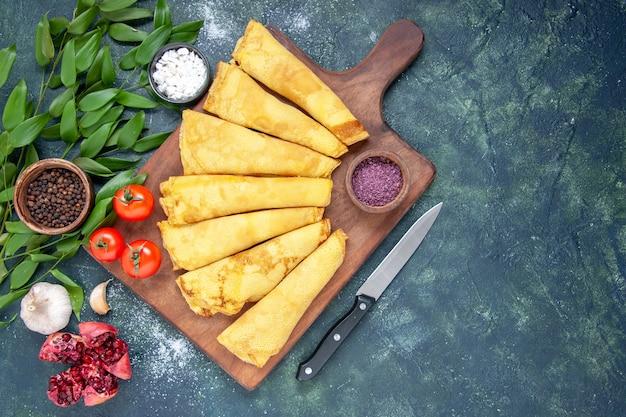 Draufsicht leckere pfannkuchen gerollt auf dunkelblauem hintergrund gebäck hotcake teig kuchen fleischfarbe süße kuchenmahlzeit