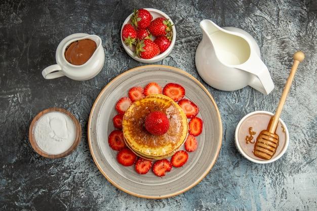 Draufsicht leckere pfannkuchen mit erdbeeren und honig auf dem licht