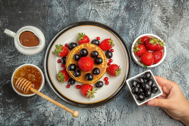 Draufsicht leckere pfannkuchen mit frischen früchten und honig auf licht
