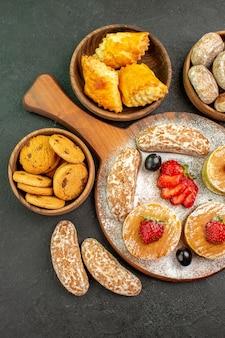 Draufsicht leckere pfannkuchen mit früchten und süßen kuchen im dunkeln