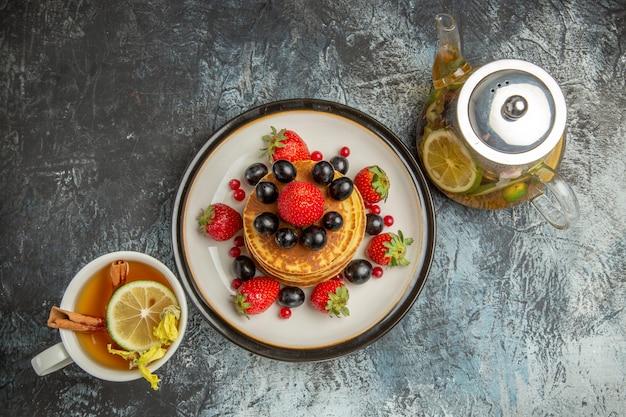 Draufsicht leckere pfannkuchen mit früchten und tee auf licht