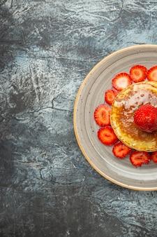 Draufsicht leckere pfannkuchen mit honig und erdbeeren auf licht