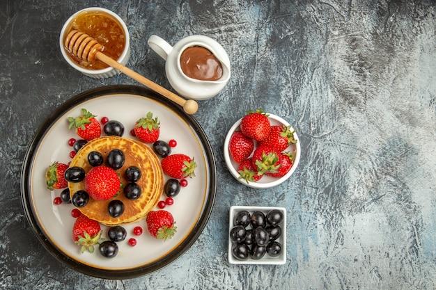 Draufsicht leckere pfannkuchen mit honig und früchten auf dem licht