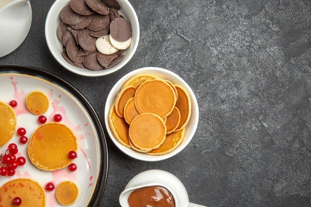 Draufsicht leckere pfannkuchen mit keksen auf dem grauen hintergrund