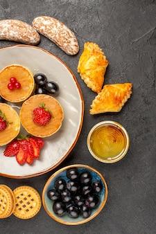 Draufsicht leckere pfannkuchen mit kuchen und früchten auf dunkelheit