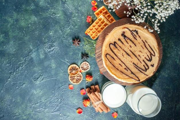 Draufsicht leckere pfannkuchen mit milch auf dunkelblauer oberfläche