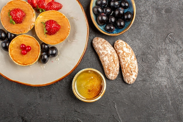 Draufsicht leckere pfannkuchen mit obst und kuchen auf dunklem boden