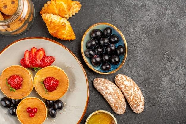 Draufsicht leckere pfannkuchen mit obst und kuchen im dunkeln