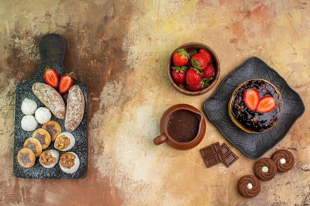 Draufsicht leckere pfannkuchen mit süßigkeiten und früchten auf holzschreibtisch