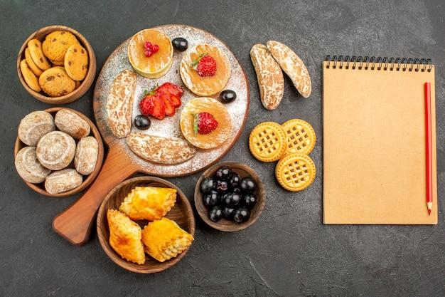 Draufsicht leckere pfannkuchen mit verschiedenen süßigkeiten auf dunklem schreibtischzuckerkuchen-dessert