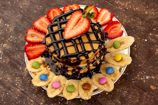 Draufsicht leckere pfannkuchen schokolade mit geschnittenen roten erdbeeren und bananen in weißen teller auf dem braunen schreibtisch
