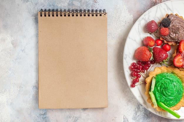Draufsicht leckere sahnekuchen mit früchten auf leichten tischkekskuchen-dessertbonbons