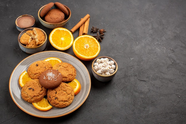 Draufsicht leckere sandkekse mit frisch geschnittenen orangen auf dunklem hintergrund obstkeks süßer keks zitruszucker