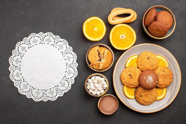 Draufsicht leckere sandkekse mit geschnittenen orangen auf dem dunklen hintergrund obst zitrus keks süßer kuchen keks