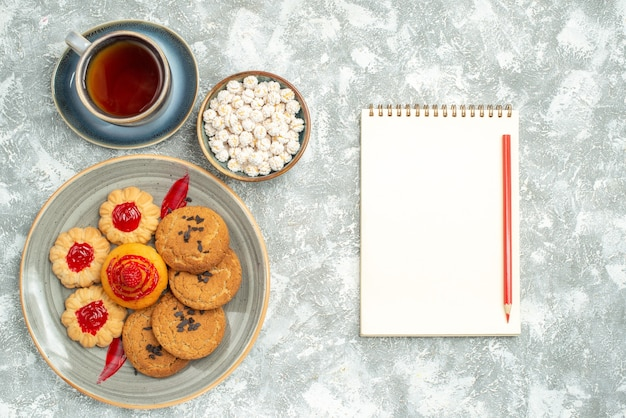 Draufsicht leckere sandkekse mit keksen und tasse tee auf weiß