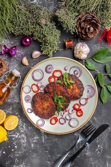 Draufsicht leckere schnitzel mit zwiebelringen auf grauem schreibtisch fleischgericht mahlzeit foto