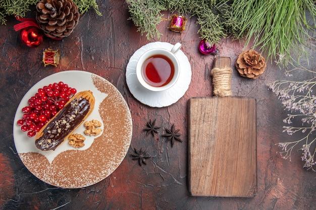 Draufsicht leckere schoko-eclairs mit beeren und tee auf dunklem tischkuchen-kuchen-nachtisch süß