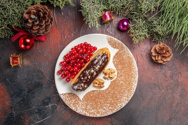 Draufsicht leckere schoko-eclairs mit roten beeren auf dem dunklen tischkuchen-kuchen-nachtisch süß