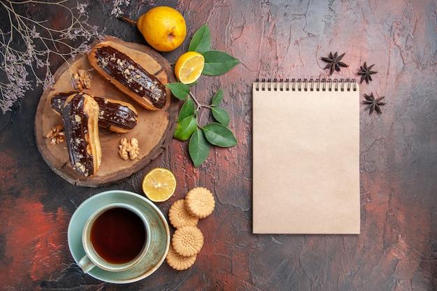 Draufsicht leckere schoko-eclairs mit tasse tee auf dunklem boden nachtisch süßer kuchen