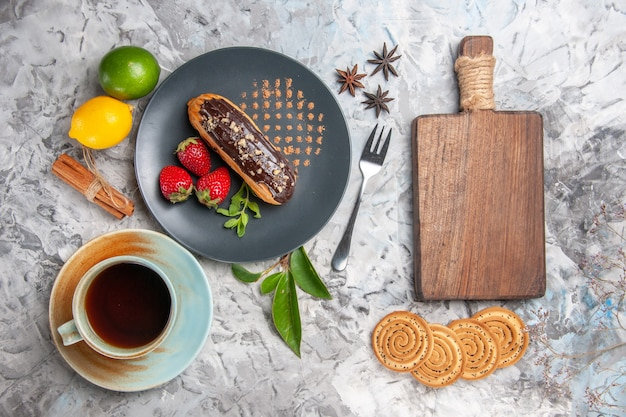 Draufsicht leckere schoko-eclairs mit tasse tee auf hellem kekskuchen-dessert